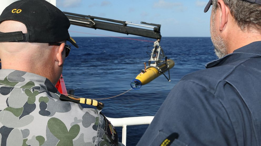 "PHOTO: In this handout image provided by the Australian Department of Defense, Commander James Lybrand and Chris ""Sharkie"" Moore, watch the launching the Phoenix Autonomous Underwater Vehicle Artemis off the deck of ADV Ocean Shield on April 17, 2014."