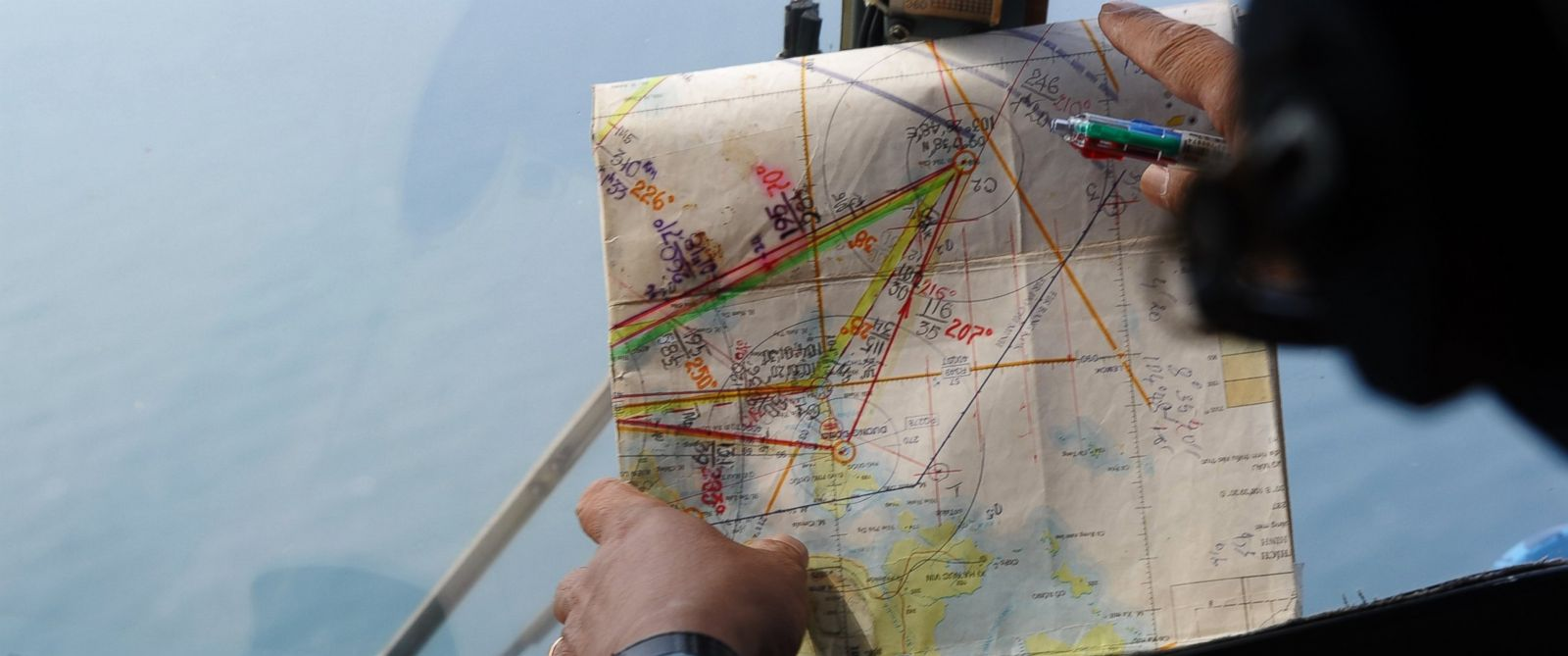 PHOTO: A crew member aboard a Vietnamese Air Force helicopter checks a map during a search flight for evidence of the missing Malaysia Airlines MH370 over the southern Vietnamese waters on March 11, 2014.