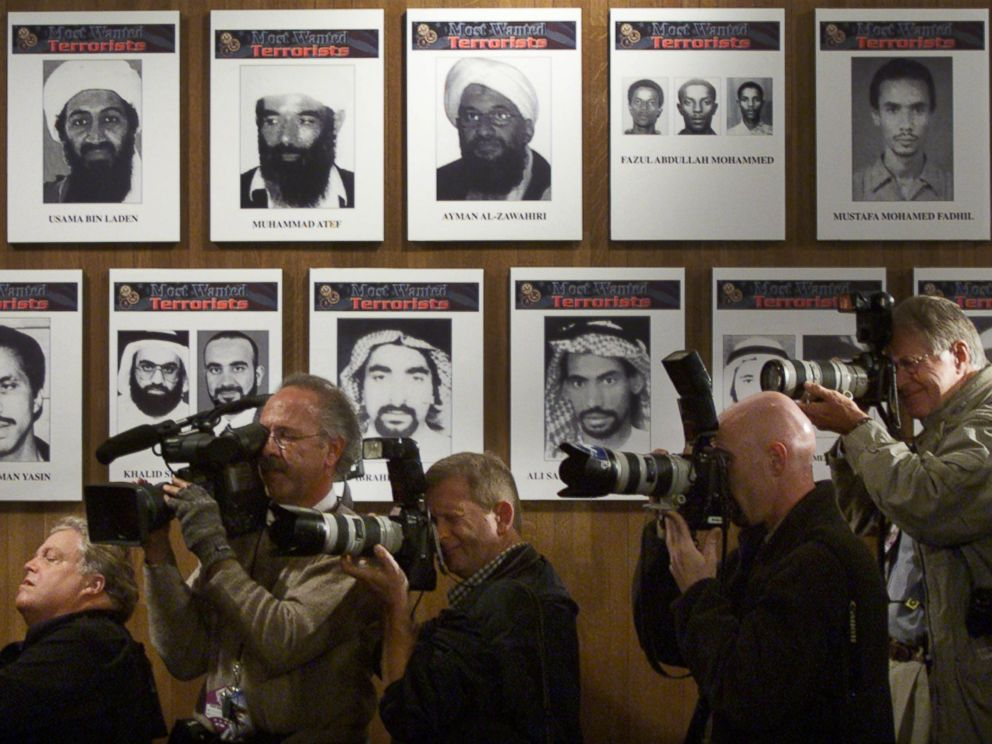 PHOTO: Members of the media stand next to a wall of the Most Wanted terrorists as U.S. President George W. Bush announces a new list of the FBIs Most Wanted, placing Osama Bin Laden is at the top of the list Oct. 10, 2001 in Washington, D.C.
