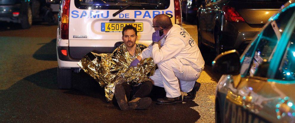 PHOTO: A medic tends to a man near the Boulevard des Filles-du-Calvaire after an attack, Nov. 13, 2015 in Paris.