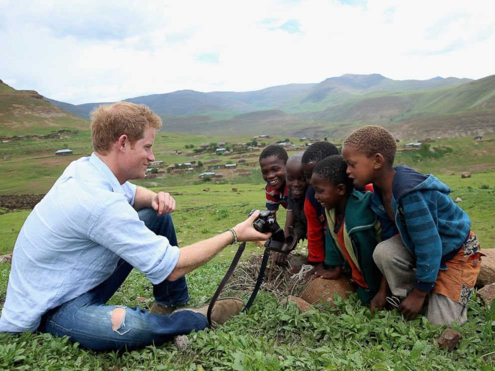 PHOTO: Prince Harry shows children a photograph he has taken on a digital camera during a visit to a herd boy night school constructed by Sentebale on Dec. 8, 2014 in Mokhotlong, Lesotho.