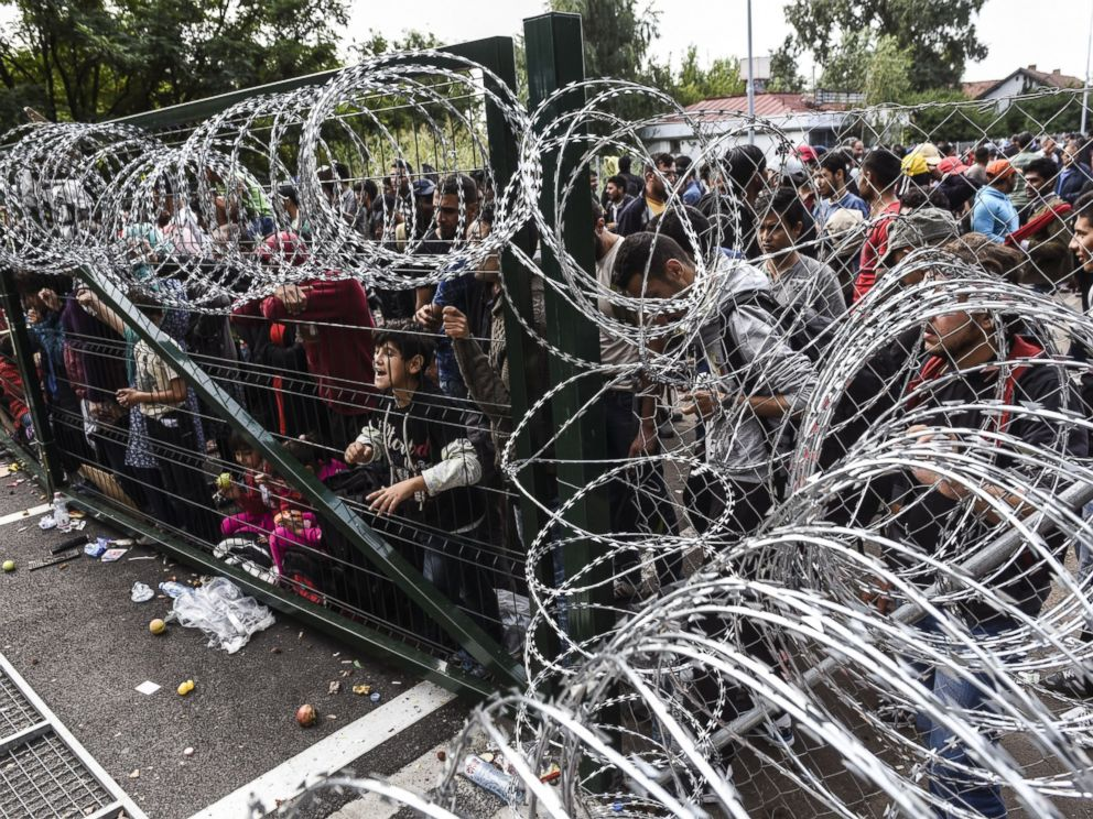 PHOTO: Refugees stand behind a fence at the Hungarian border with Serbia near the town of Horgos on Sept. 16, 2015.