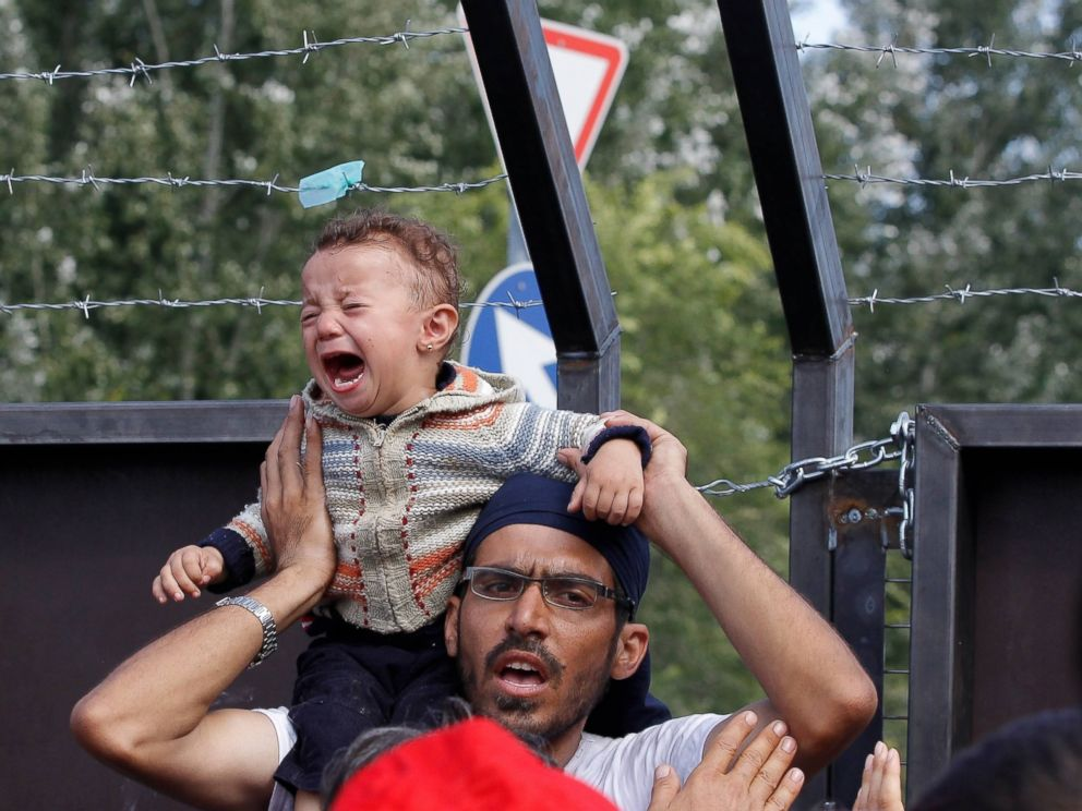 PHOTO: A refugee holds his baby on his shoulders as refugees continue waiting on the Hungarian border in Horgos, Serbia after authorities closed the border on Sept. 16, 2015.
