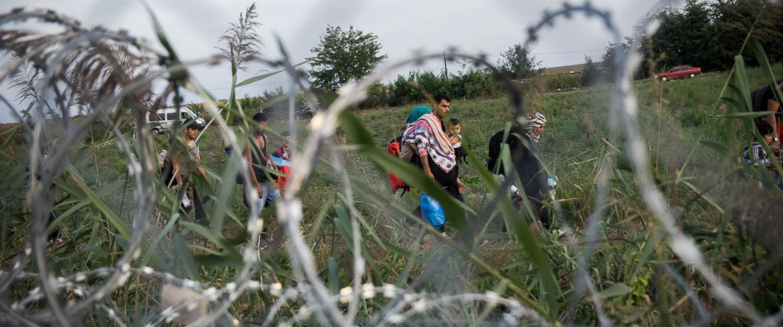 PHOTO: Refugees walk along a barbed wire barrier a the border of Hungary and Serbia, near Roszke, Hungary, Sept. 14, 2015.