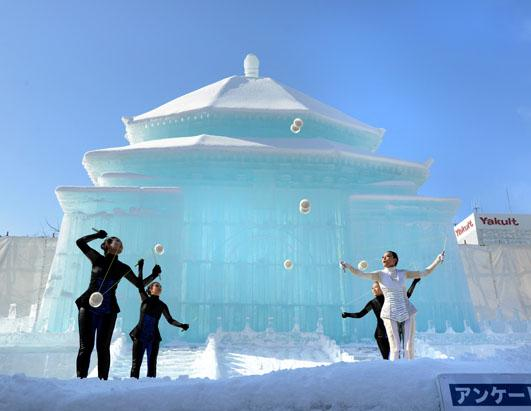 taiwanese dancers perform in front of a large snow sculpture of taipei