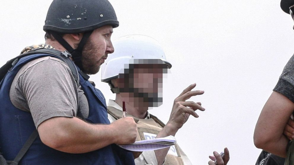 PHOTO: In this handout image made available by the photographer Etienne de Malglaive, American journalist Steven Sotloff (center with black helmet) talks to Libyan rebels