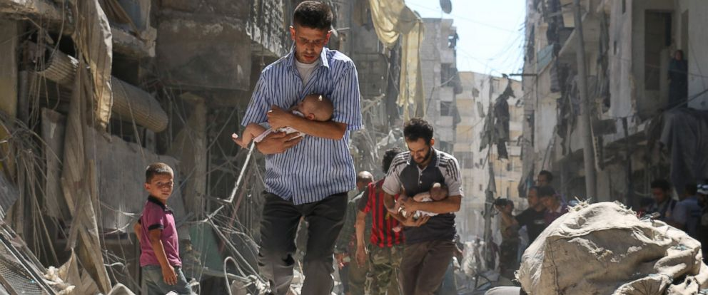 PHOTO: Syrian men carrying babies make their way through the rubble of destroyed buildings following a reported air strike on the rebel-held Salihin neighbourhood of the northern city of Aleppo on Sept. 11, 2016.