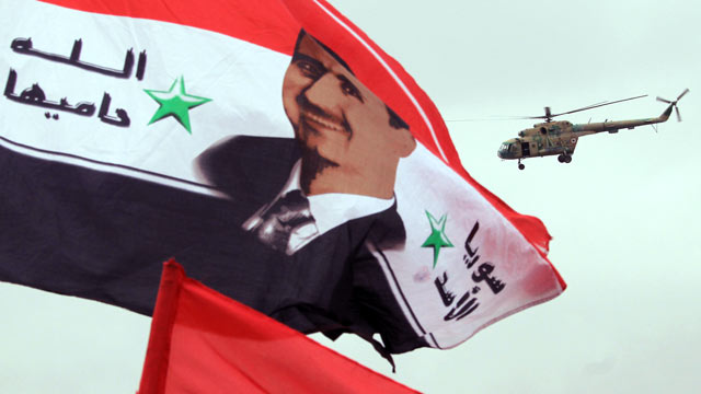 PHOTO: A Syrian army helicopter hovers above a national flag bearing a portrait of Syrian President Bashar al-Assad, in this Jan. 11, 2012 file photo.