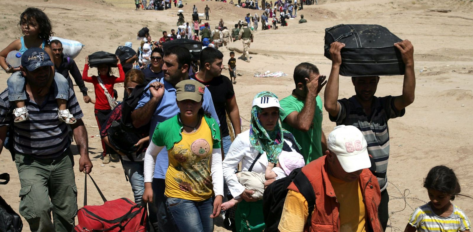 PHOTO: Syrian refugees cross the border into the autonomous Kurdish region of northern Iraq, on August 17, 2013.