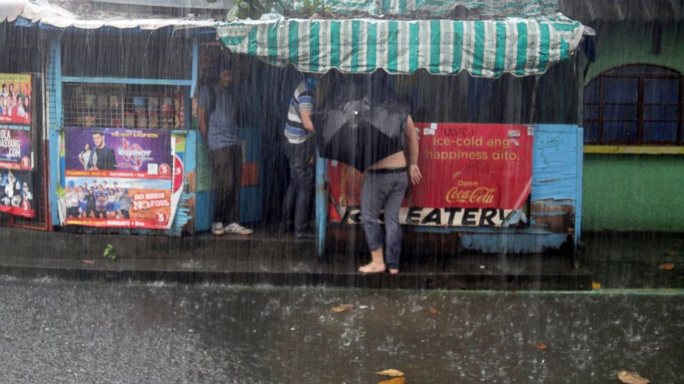 PHOTO: A Filipino holding a black umbrella walks along a narrow path leading to an eatery in suburban Quezon City, east of Manila, Philippines, to avoid floodwaters caused by sudden rainfall on August 3, 2015.