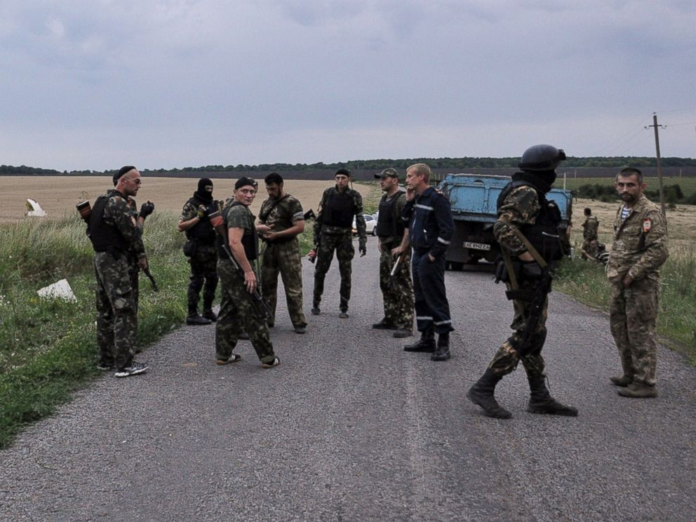 PHOTO: Men wearing military fatigues stand on a road at the site of the wreckage of a Malaysian airliner in rebel-held east Ukraine on July 17, 2014.