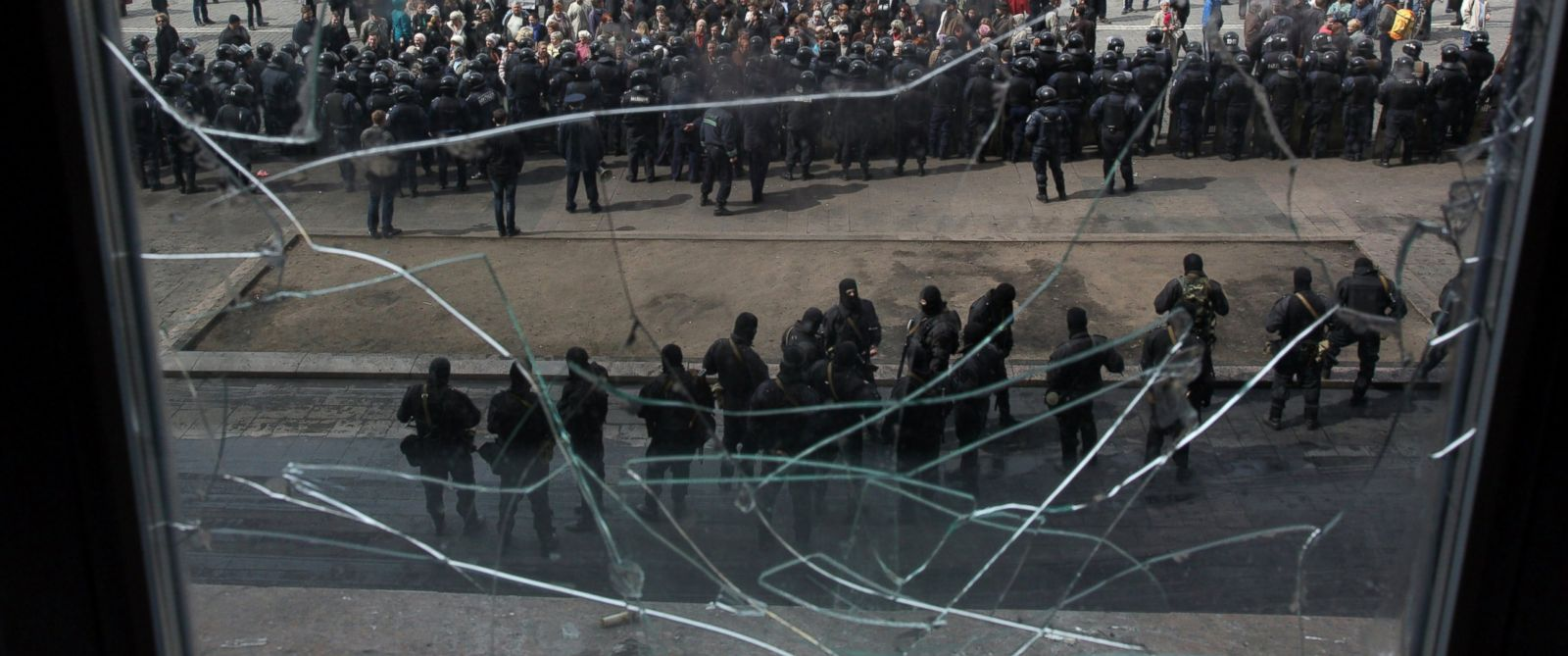 PHOTO: A photo taken through a shattered window shows pro-Russian protesters gathered in front of Ukrainian police officers, who are standing guard of the Kharkiv regional state administration building on April 8, 2014.