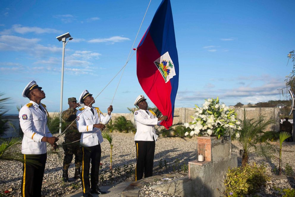 PHOTO: National police officers raise a Haitian national flag during a memorial service honoring the victims of the 2010 earthquake, at Titanyen, a mass burial site north of Port-au-Prince, Haiti, Jan. 12, 2018.