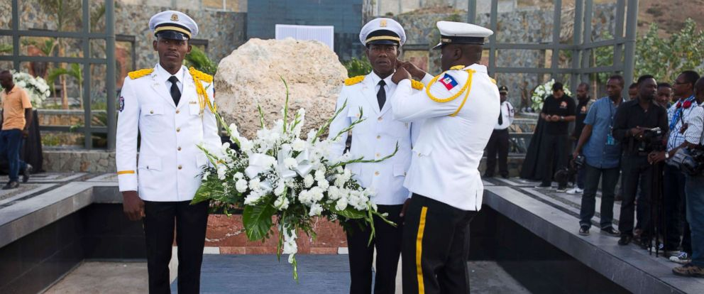 PHOTO: National police officers holding a flower wreath wait for the arrival of Haitis President Jovenel Moise to begin a memorial service honoring the victims of the 2010 earthquake, at a mass burial site in Port-au-Prince, Haiti, Jan. 12, 2018.