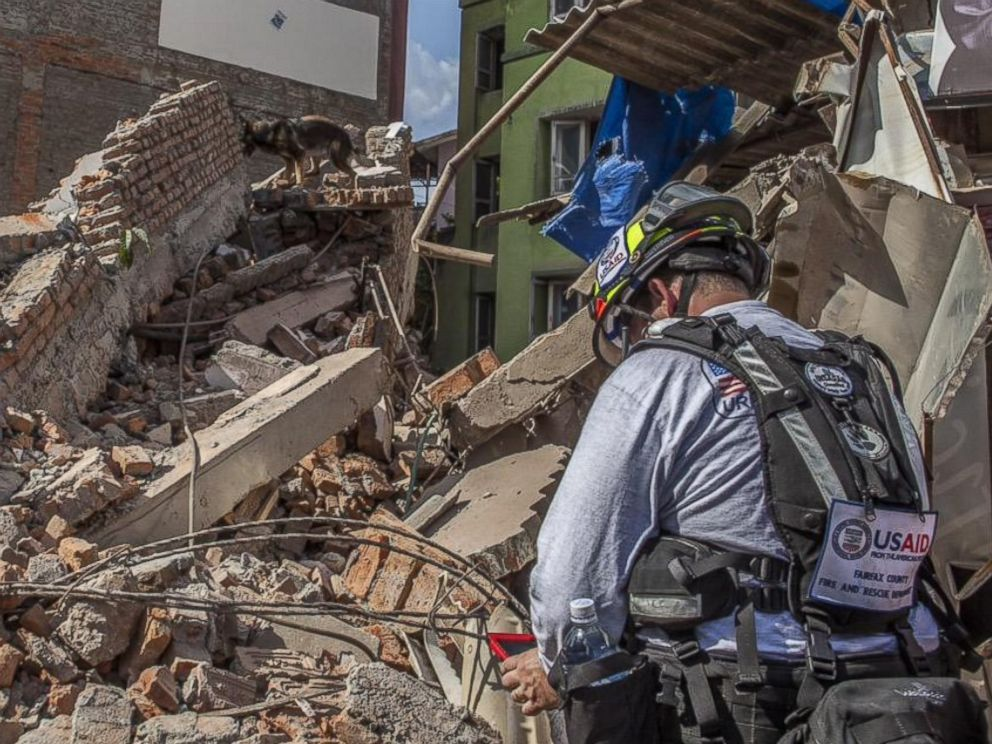 PHOTO: Members of a USAID Dart canine team work to find people trapped under a building that collapsed in Naya Bazaar, Nepal after an earthquake hit on May 12, 2015.