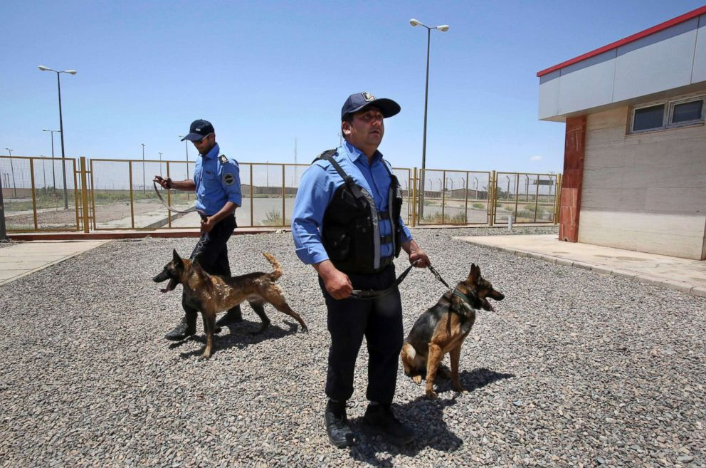 PHOTO: Two Iranian custom officers hold their drug-sniffing dogs at Irans Dogharoun customs house on border with Afghanistan, near Taibad in eastern Iran, June 1, 2014.