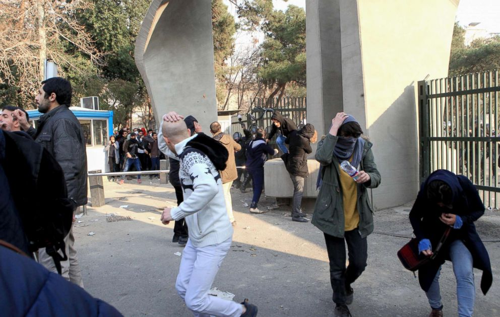 PHOTO: Iranian students run for cover from tear gas at the University of Tehran during a demonstration driven by anger over economic problems, in the capital Tehran, Dec. 30, 2017.