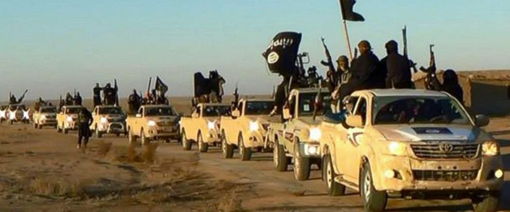PHOTO: In this undated file photo released online in the summer of 2014 which has been verified and is consistent with other AP reporting, ISIS militants hold up their weapons and wave flags in a convoy on a road leading to Iraq, in Raqqa, Syria.