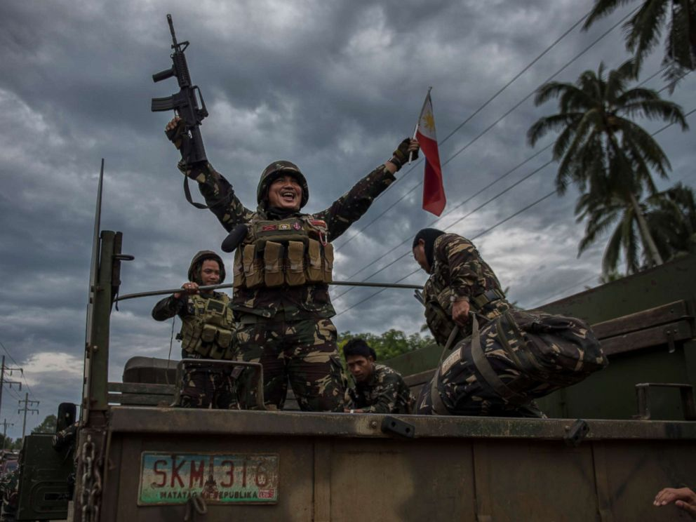 PHOTO: A government soldier waving the Philippine flag as they get ready to leave the battle against IS-inspired militants, Oct. 20, 2017, in Saguiaran town in Lanao del Sur, southern Philippines.
