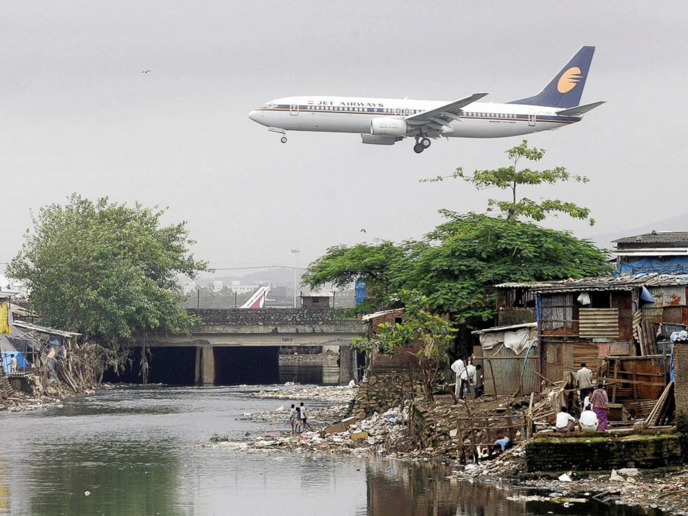 PHOTO: A Jet Airways plane flies over the Mithi River on its way to landing at Mumbai airport, at Bharat Nagar, Aug. 16, 2005 in Hyderabad, India.