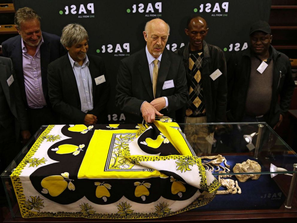PHOTO: Ron Clarke, a professor from the Evolutionary Studies Institute at the University of the Witwatersrand, center, unveils the virtually complete Australopithecus fossil Little Foot in Johannesburg, South Africa, Dec. 6, 2017.