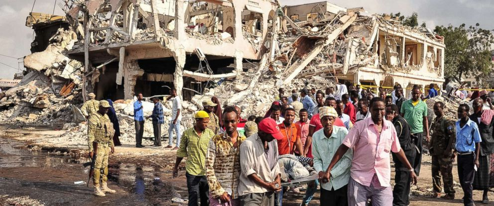 PHOTO: Men carry the body of a victim of a truck bomb explosion the day after the attack that occurred in the center of Mogadishu outside a hotel on Oct. 14, 2017.