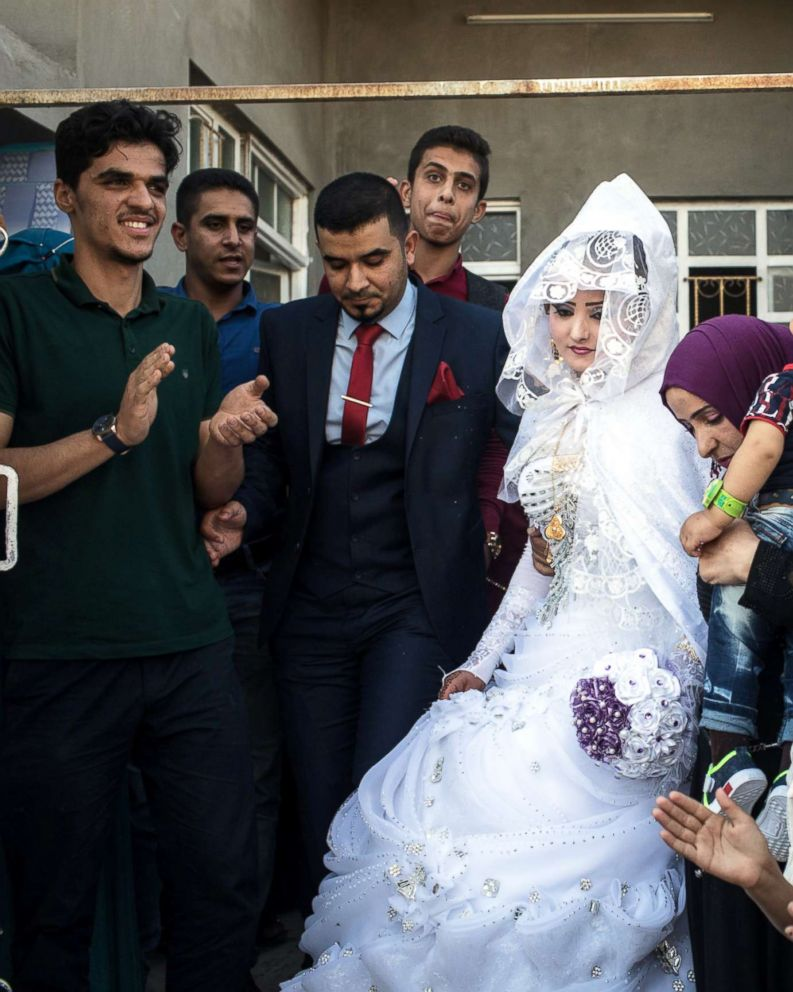 PHOTO: Family members watch on as a bride and groom leave their house to be married in West Mosul on Nov. 3, 2017.