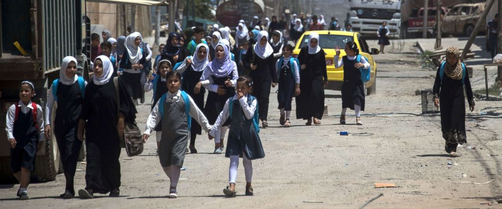PHOTO: Iraqi girls walk back from school in west Mosul, July 12, 2017, after the government declared it had driven the Islamic State (IS) group jihadists from their one-time top stronghold.
