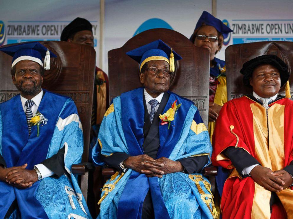 PHOTO: Zimbabwes President Robert Mugabe, center, sits for formal photographs with university officials, after presiding over a student graduation ceremony at Zimbabwe Open University on the outskirts of Harare, Zimbabwe, Nov. 17, 2017.
