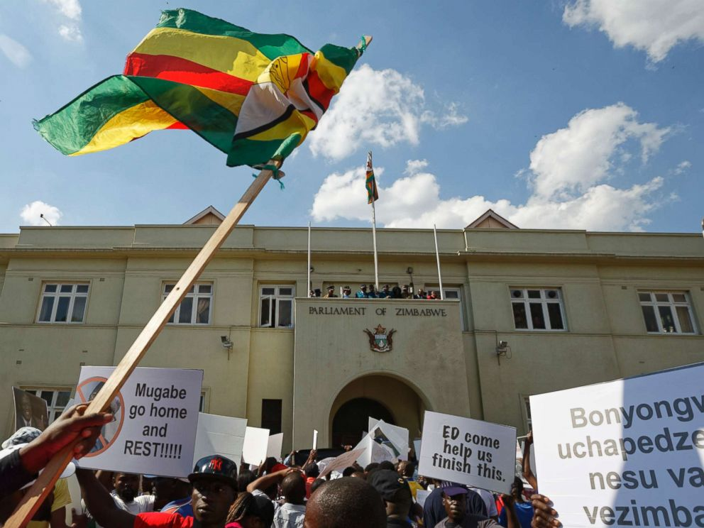 PHOTO: Protesters calling for the impeachment of President Robert Mugabe brandish a national flag as they demonstrate outside the parliament building in Harare, Zimbabwe, Nov. 21, 2017.