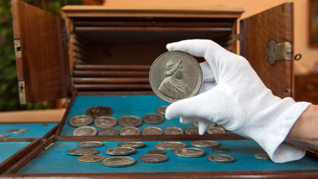 PHOTO: A hand holds a coin with Cardinal Clemens XI  at the State Library in Passau, Germany, Dec. 7, 2011.