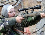 PHOTO: A female Syrian rebel looks through the riflescope of her sniper rifle in Aleppo, Syria, Jan. 25, 2013.