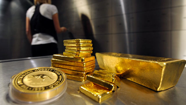 PHOTO: A staff member of the private coin and precious metal dealer pro aurum opens a safe while gold bars and coins are seen in the front in Munich, Germany, Aug, 31 2011.