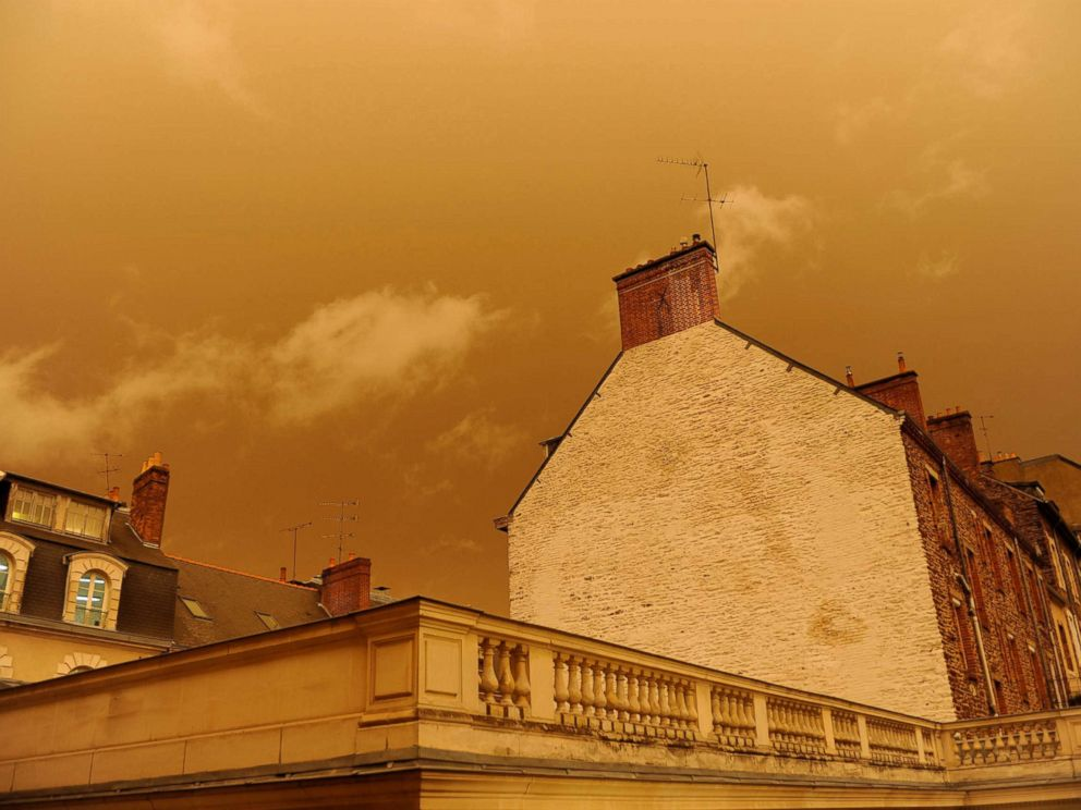 PHOTO: Rooftops under an yellow-ochre sky in central Rennes, western France, Oct. 16, 2017.