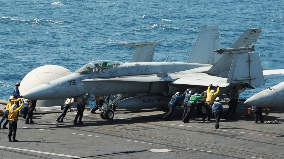 PHOTO: Sailors guide an F/A-18C Hornet assigned to the Valions of Strike Fighter Squadron (VFA) 15 on the flight deck of the aircraft carrier USS George H.W. Bush (CVN 77) on Aug. 8, 2014.