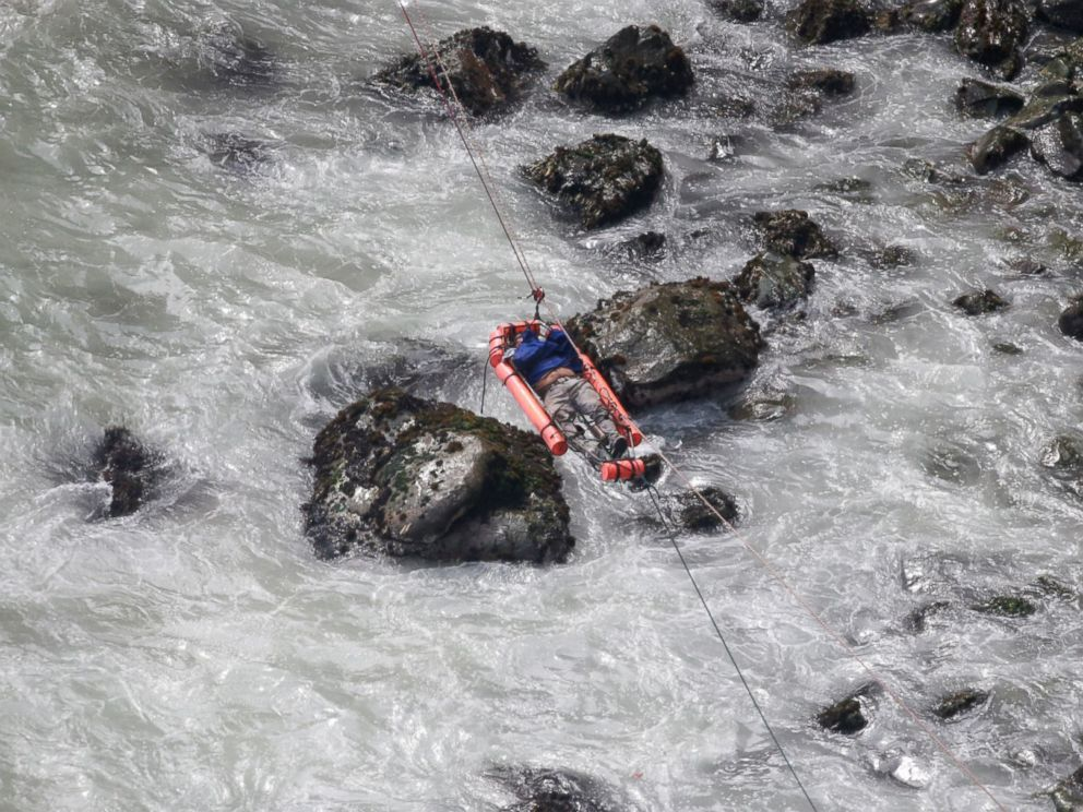 PHOTO: An injured man is transported over water from a bus that fell off a cliff after it was hit by a tractor-trailer rig, in Pasamayo, Peru, Jan. 2, 2018.