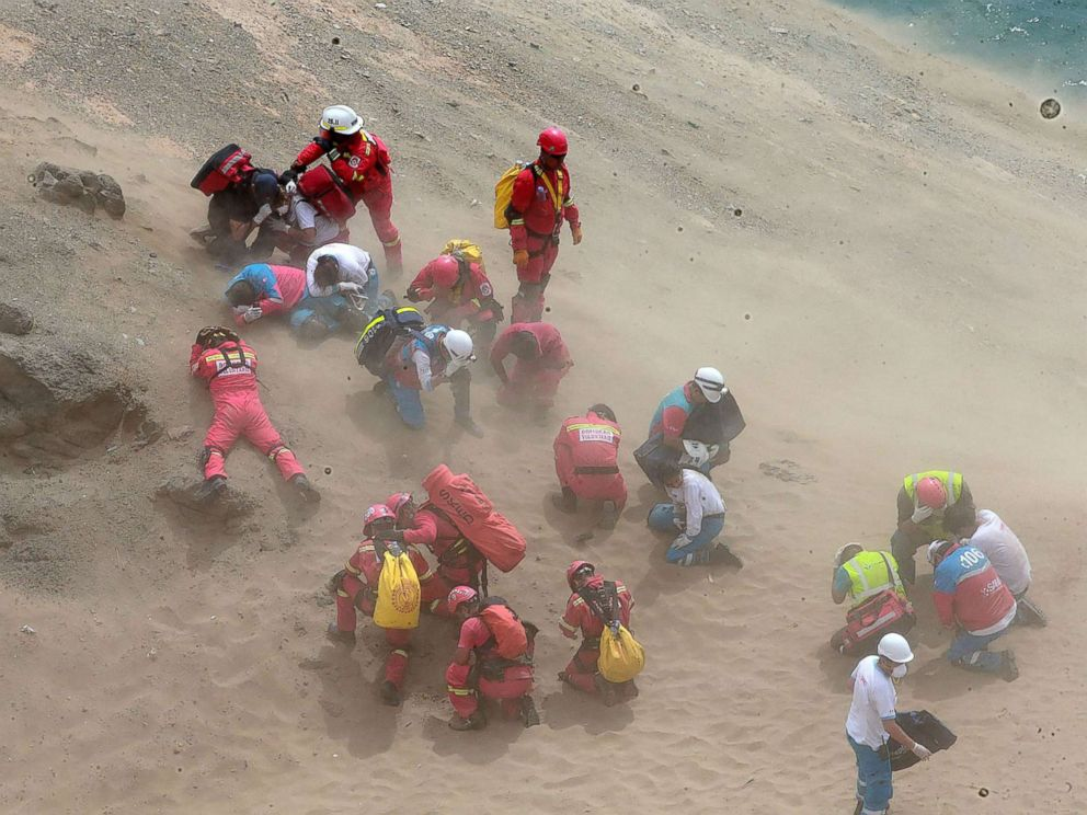 PHOTO: Emergency personnel covering themselves from dust generated by a helicopter during rescue operations after a passenger bus plunged off the Pan-American Highway North, outside of Lima, Peru, Jan. 2, 2018.