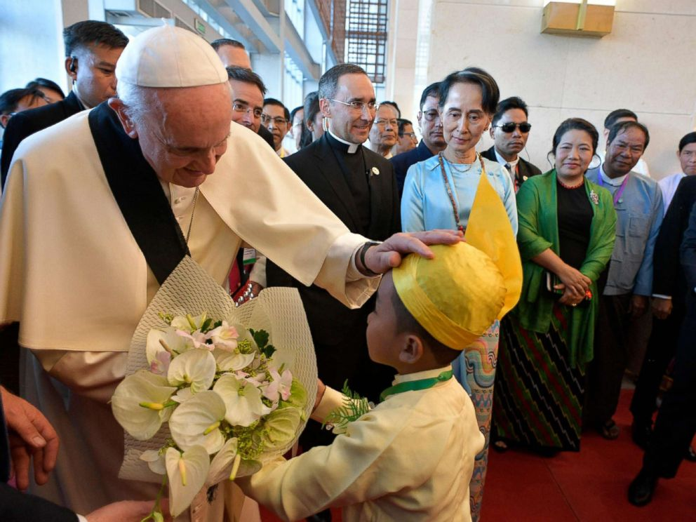 PHOTO: This handout picture taken and released by the Vatican press office (Osservatore Romano) on Nov. 28, 2017, shows Pope Francis greeting a child as Myanmars civilian leader Aung San Suu Kyi watches during an event in Naypyidaw.