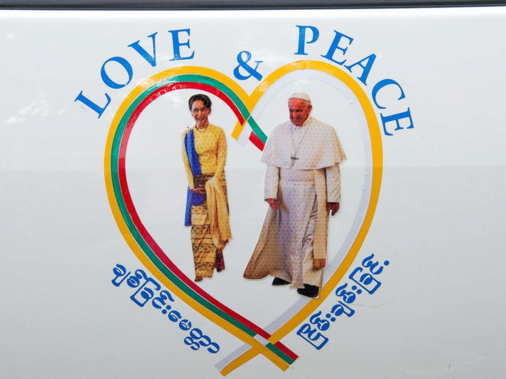 PHOTO: A sticker of Myanmars State Counselor Aung San Suu Kyi (L) and Pope Francis is displayed on a car in the streets of downtown Yangon, after the popes arrival in Myanmar for a four-day official visit on Nov. 27, 2017.