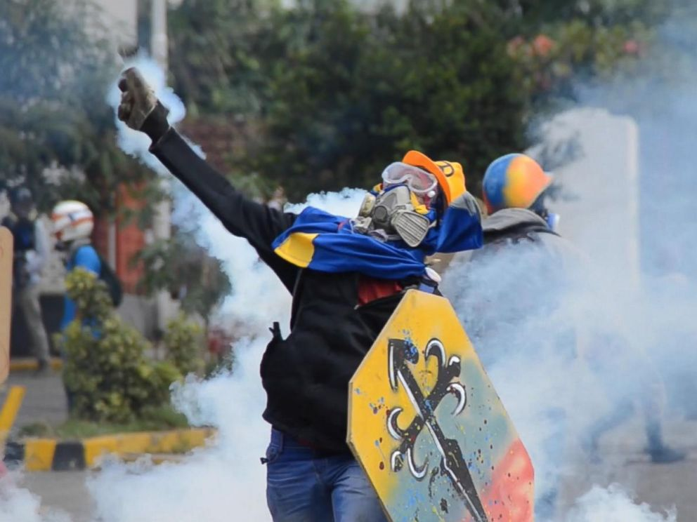 PHOTO: An anti-government demonstrator throws back a tear gas cannister launched by police forces, in Caracas, Venezuela.