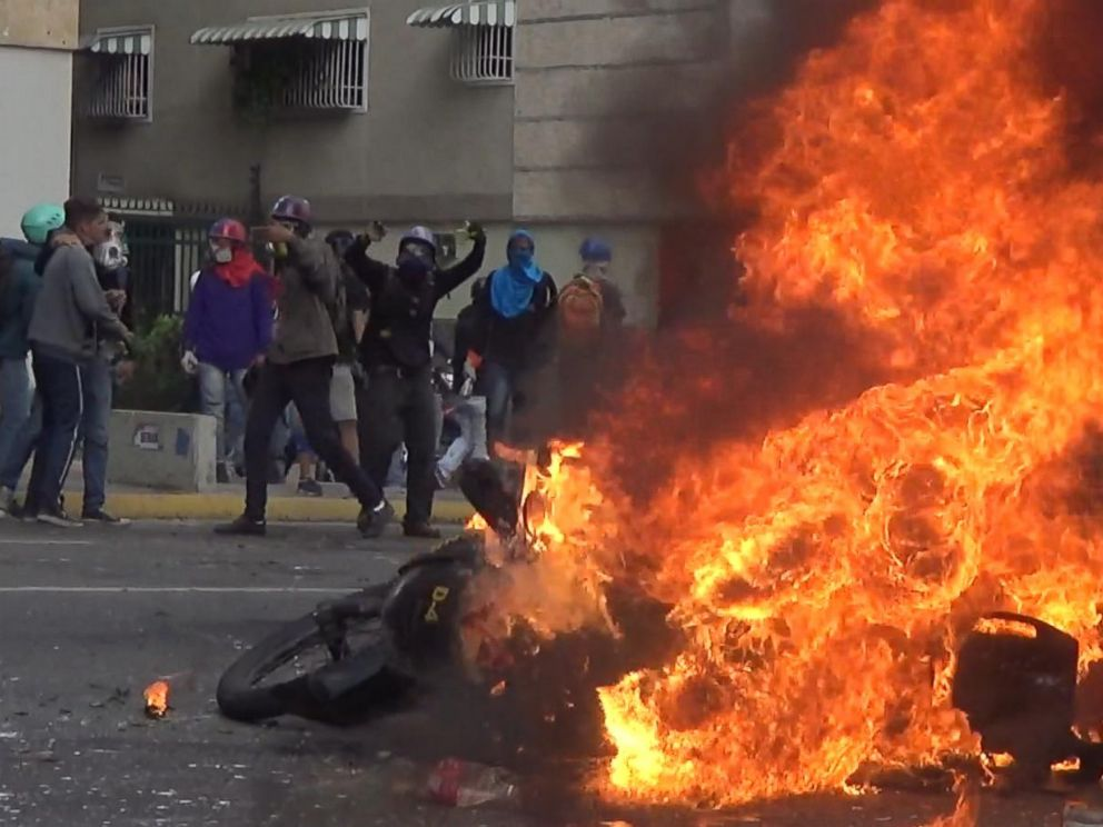 PHOTO: A police motorcycle burns in the streets of Caracas, Venezuela.