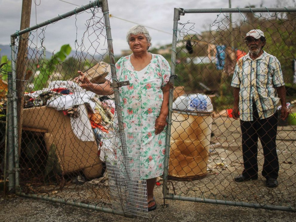 PHOTO: Luz Sota Rivera (C) and Francisco Nazario Aviles pose outside their damaged home, with debris removed from their home uncollected in the driveway, three weeks after Hurricane Maria hit the island, Oct. 12, 2017 in Jayuya, Puerto Rico.