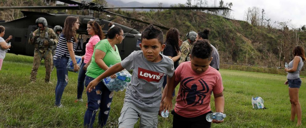PHOTO: Boys carry water away from an HH-60 Blackhawk helicopter after soldiers working with the U.S. Army dropped off relief supplies during recovery efforts following Hurricane Maria, in Jayuya, Puerto Rico, October 5, 2017.