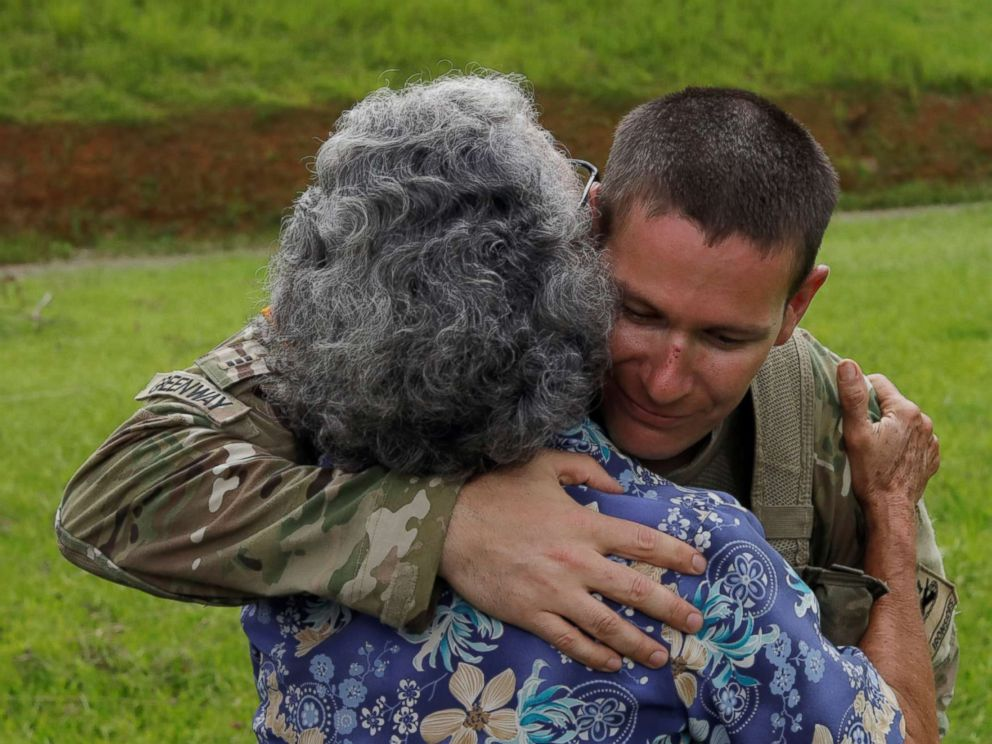 PHOTO: UH-60 Blackhawk helicopter pilot Chris Greenway receives a hug from a woman thanking him for water during recovery efforts following Hurricane Maria, in Verde de Comerio, Puerto Rico, Oct. 7, 2017.