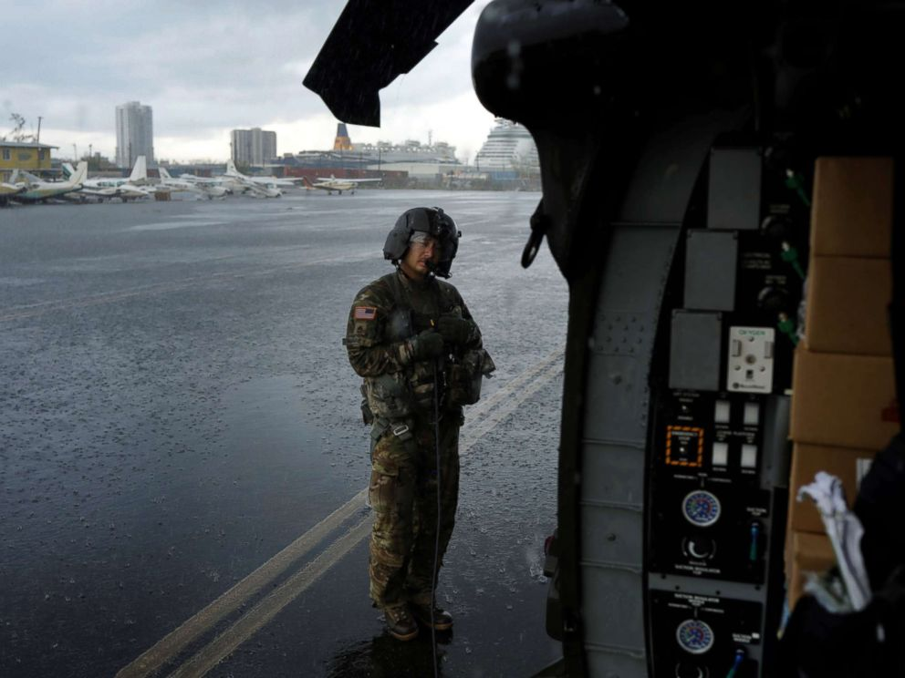 PHOTO: Crew chief Kenney shelters under the blade of an HH-60 Blackhawk helicopter from 101st Airborne Divisions Dustoff unit preparing to take off during recovery efforts following Hurricane Maria, in Isla Grande, Puerto Rico, Oct. 6, 2017.