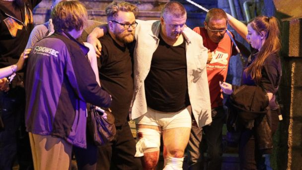 PHOTO: People aid an injured man near the Manchester Arena after reports of an explosion, May 22, 2017.