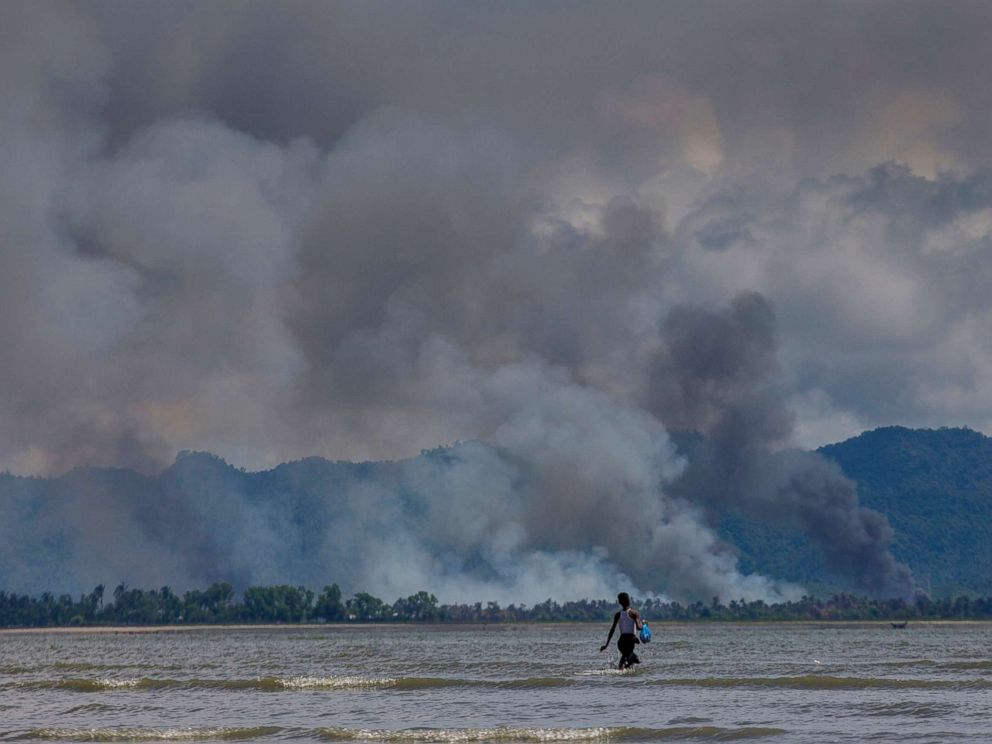 PHOTO: A Bangladeshi boy walks towards a parked boat as smoke rises from across the border in Myanmar, at Shah Porir Dwip, Bangladesh, Sept. 14, 2017.