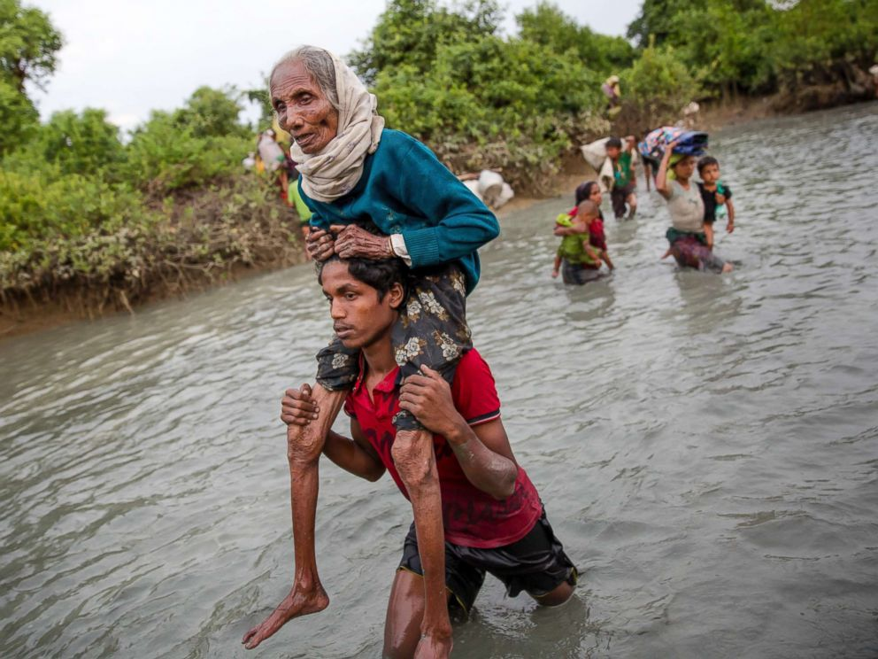 PHOTO: A Rohingya Muslim man carries an elderly woman through water after crossing the border from Myanmar into Bangladesh, near Palong Khali, Bangladesh on Nov. 1, 2017.