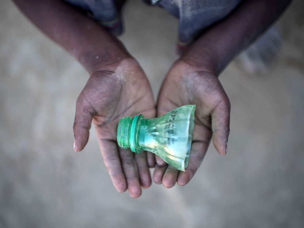 Shahidul Amin, who arrived in Bangladesh in September holds a part of a bottle that he uses to play in the sand at the Thankhali refugee camp in Coxs Bazar on Dec. 2 2017