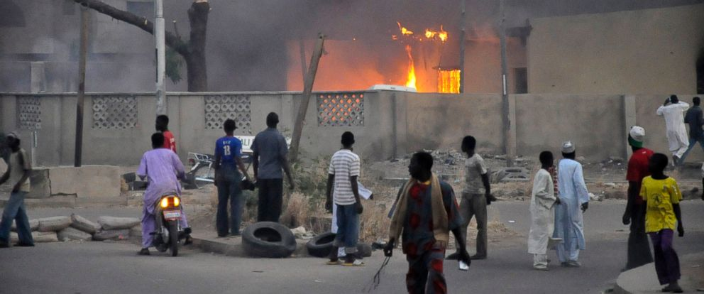 PHOTO: People watch as smoke rises from the police headquarters after it was hit by a blast in Nigerias northern city of Kano, in this Jan. 20, 2012 file photo.